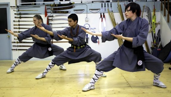 Atado School of Defensive Arts Shifus in Shaolin robes demonstrate a Kung Fu pose in front of the weapons wall